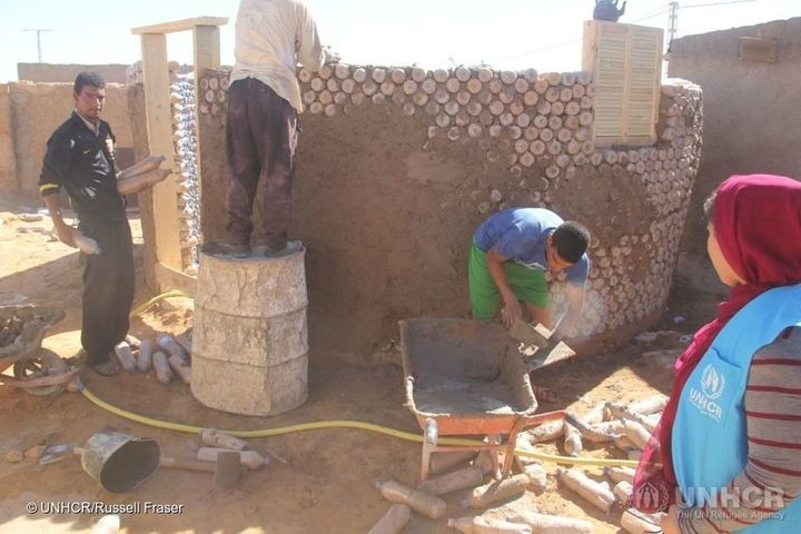 building a home using sand-filled plastic bottles for new refugees in SE Algeria